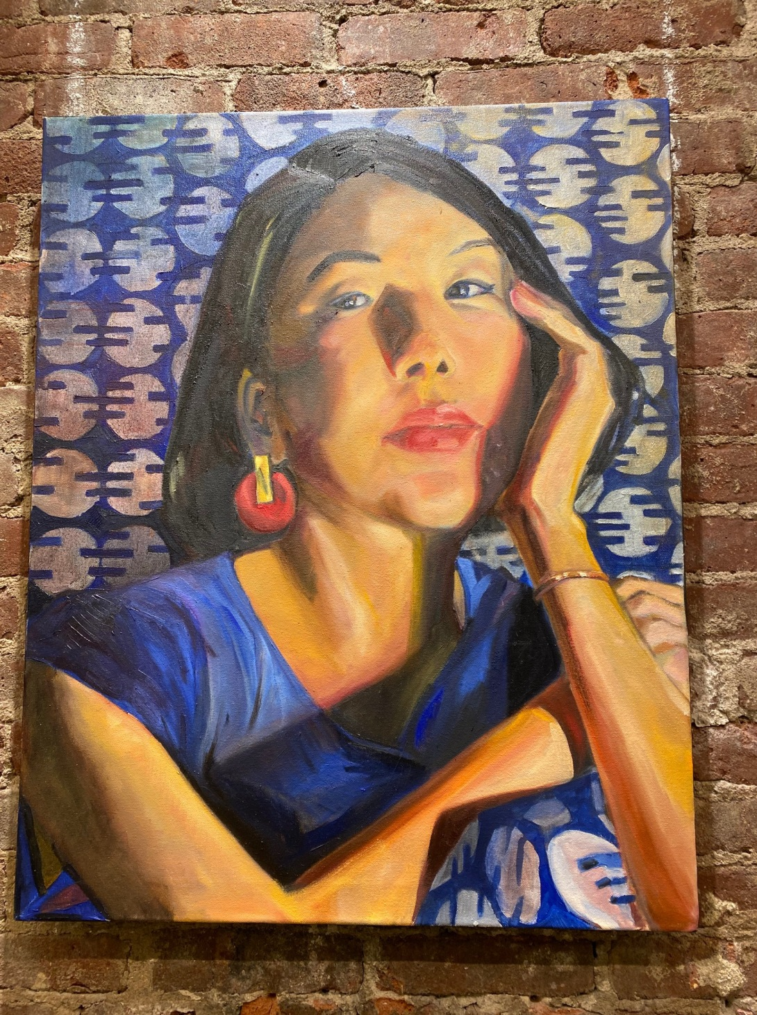 Image of an Asian woman painted against a blue and white pattern backgroundby artist Marguerite Wibaux